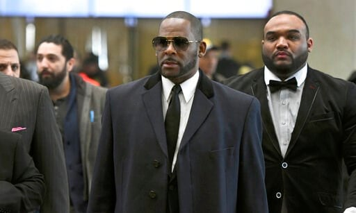 (AP Photo/Matt Marton, File). FILE - In this May 7, 2019 file photo, Musician R. Kelly, center, arrives at the Leighton Criminal Court building for a hearing in Chicago. Prosecutors charged R&B singer R. Kelly on Thursday, May 30, with 11 new sex-r...