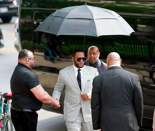 (AP Photo/Amr Alfiky). Musician R. Kelly, center, arrives at the Leighton Criminal Court building for an arraignment on new sex-related felonies Thursday, June 6, 2019, in Chicago. Thursday's hearing comes a week after prosecutors announced the new cou...