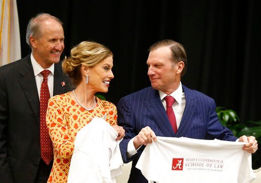(Gary Cosby Jr./The Tuscaloosa News via AP). In this Sept. 20, 2018, photo, Hugh F. Culverhouse Jr., right, and wife, Eliza, in Tuscaloosa, Ala., show off T-shirts from the the University of Alabama law school, which now bears his name. The university ...
