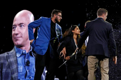 (AP Photo/John Locher). Security removes a protestor, second from left, from the stage as Amazon CEO Jeff Bezos speaks at the the Amazon re:MARS convention, Thursday, June 6, 2019, in Las Vegas.