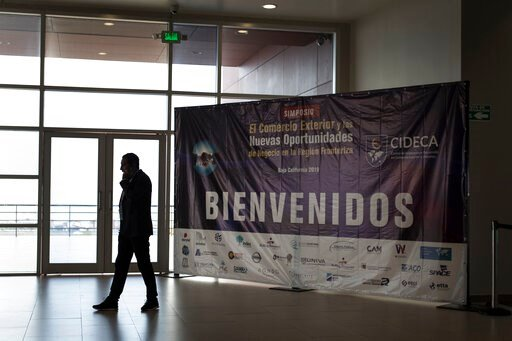 """(AP Photo/Hans-Maximo Musielik). A business man talks on the phone next to the welcome sign of the """"New Opportunities for Foreign Trade"""" Symposium at the Rosarito Convention Center near Tijuana, Mexico, Friday, June 7, 2019. Companies have been rushing..."""