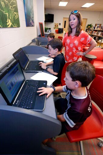 (AP Photo/Rogelio V. Solis). In this May 8, 2019, photograph, Sharon Stidham, standing, talks to her sons Graham, center, and Miles, front, as they use the laptops at East Webster High School to do homework in Maben, Miss. A cellphone tower is visible ...