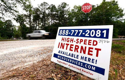 (AP Photo/Rogelio V. Solis). In this May 8, 2019, photo, a car drives past a sign advertising high-speed internet service near Starkville, Miss. In classrooms, access to laptops and the internet is nearly universal. But many students struggle to keep u...