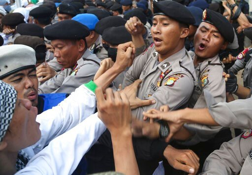 (AP Photo/Tatan Syuflana, File). FILE - In this Nov. 22, 2013, file photo, Indonesian police officers block members of the militant Islamic Defenders Front (FPI) during a demonstration outside Australian Embassy in Jakarta. The Islamic Defenders Front,...