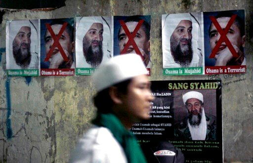 (AP Photo/Irwin Fedriansyah, File). FILE - In this May 4, 2011, file photo, a member of radical group Islam Defenders Front walks past posters of Osama Bin laden and U.S. President Barack Obama, during prayers for the al-Qaida leader at their headquart...