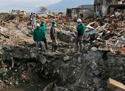 (AP Photo/Dita Alangkara). In this Oct. 2, 2018 photo, volunteers of the humanitarian wing of the Islamic Defenders Front examine the damage caused by the earthquake and liquefaction at Balaroa neighborhood in Palu, Central Sulawesi, Indonesia Indonesi...