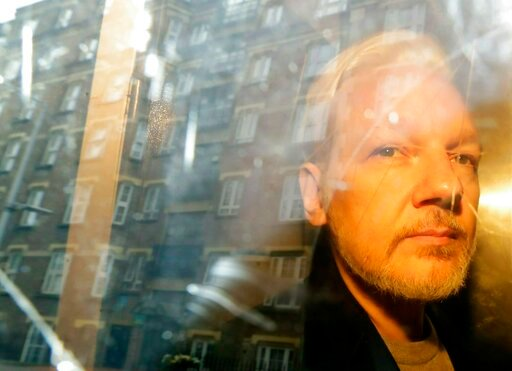 (AP Photo/Matt Dunham, File). FILE - In this Wednesday, May 1, 2019 file photo, buildings are reflected in the window as WikiLeaks founder Julian Assange is taken from court, where he appeared on charges of jumping British bail seven years ago, in Lond...