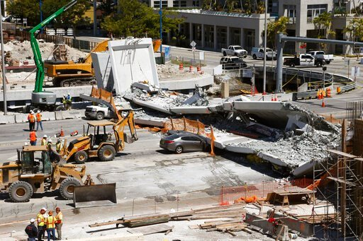 (AP Photo/Wilfredo Lee). FILE - In this March 16, 2018 file photo crushed cars are shown under a section of a collapsed pedestrian bridge near Florida International University in the Miami area. A federal workplace safety agency says engineers had know...