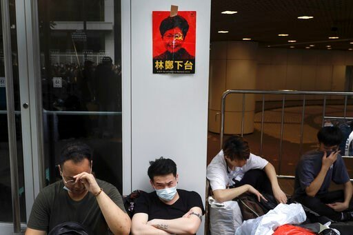 "(AP Photo/Vincent Yu). Protesters sit below a photo of Hong Kong's Chief Executive Carrie Lam with the words ""Step down"" stuck outside the Legislative Council in Hong Kong, Wednesday, June 12, 2019. Government officials in Hong Kong are bracing for a s..."