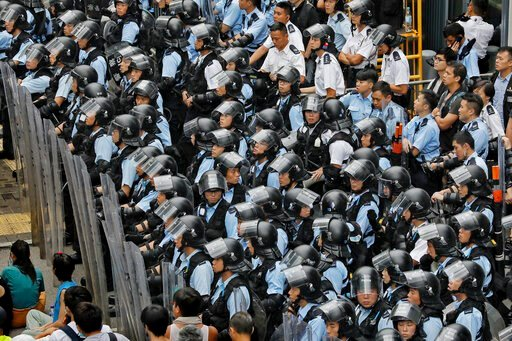 (AP Photo/Vincent Yu). Policemen in anti-riot gear stand watch as the protesters gather outside the Legislative Council in Hong Kong, Wednesday, June 12, 2019. Government officials in Hong Kong are bracing for a showdown as protesters and police contin...
