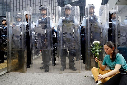 (AP Photo/Vincent Yu). A female protester holds flowers as she sits in front of policemen in anti-riot gear standing guard outside the Legislative Council in Hong Kong, Wednesday, June 12, 2019. Government officials in Hong Kong are bracing for a showd...