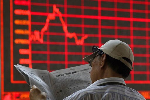 (AP Photo/Ng Han Guan). A Chinese investor reads his newspaper at a brokerage in Beijing Wednesday, June 12, 2019. Shares were mostly lower in Asia on Wednesday and Hong Kong's Seng index tumbled 1.7% as thousands continued protests against proposed le...