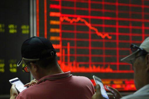 (AP Photo/Ng Han Guan). Investors check stock prices on their mobile phones near a display of the stock market index at a brokerage in Beijing on Wednesday, June 12, 2019. Shares were mostly lower in Asia on Wednesday and Hong Kong's Seng index tumbled...