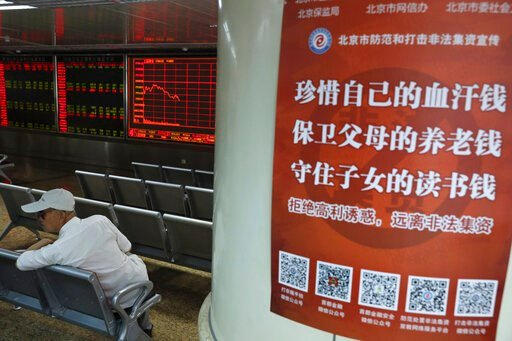 "(AP Photo/Ng Han Guan). A Chinese investor sits near a poster with the words ""Treasure your hard earned money, Protect your parent's retirement fund, Defend your children's education fund"" at a brokerage in Beijing Wednesday, June 12, 2019. Shares were..."