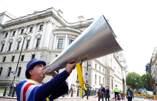 (AP Photo/Kirsty Wigglesworth). Anti Brexit campaigner Steve Bray shouts through his megaphone outside Conservative leadership contender press conferences, in London, Tuesday, June 11, 2019.