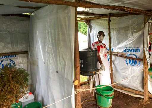 (Ben Wise/International Rescue Committee via AP). This photo taken Monday, June 10, 2019 and released by the International Rescue Committee (IRC), shows an Ebola screening checkpoint where people crossing from Congo go through foot and hand washing wit...