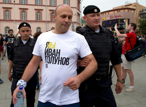 (AP Photo/Alexander Zemlianichenko). Police officers detain a supporter of Russian investigative journalist Ivan Golunov during a march in Moscow, Russia, Wednesday, June 12, 2019.