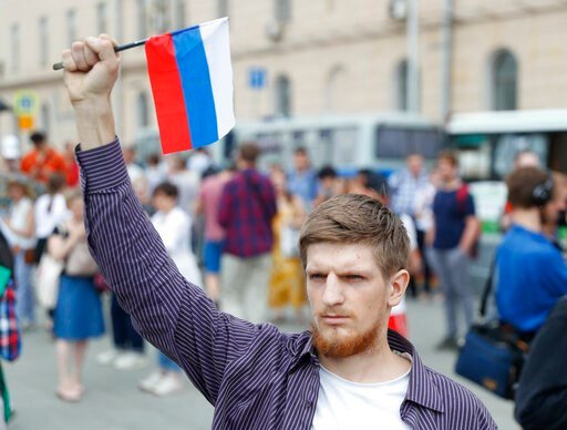 (AP Photo/Pavel Golovkin). Young mans holds a state flag as supporters of Russian investigative journalist Ivan Golunov and other protesters gather to attend a march in Moscow, Russia, Wednesday, June 12, 2019.