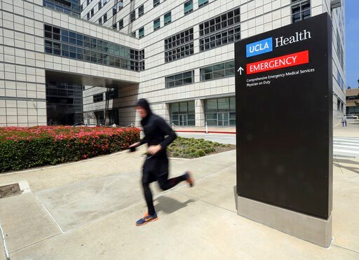 (AP Photo/Reed Saxon, File). FILE - In this April 26, 2019, file photo, a runner passes the Ronald Reagan UCLA Medical Center on the campus of the University of California, Los Angeles. A woman says she was sexually assaulted by a gynecologist who work...