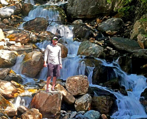 (AP Photo/Rick Bowmer). This Monday, June 10, 2019, photo shows hiker Tony Larsen posing for a photograph at a waterfalls, in the Big Cottonwood canyon, near Salt Lake City. The summer's melting snowpack is creating raging rivers that are running high,...