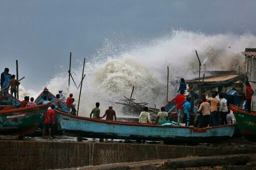 (AP Photo/Ajit Solanki). A waves crashes as people stand on boats on the Arabian Sea coast in Veraval, Gujarat, India, Wednesday, June 12, 2019. Indian authorities evacuated tens of thousands of people on Wednesday as a severe cyclone in the Arabian Se...