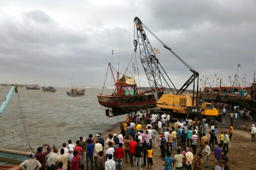 (AP Photo/Ajit Solanki). People use a crane to pull a fishing boat ashore on the Arabian Sea coast in Veraval, Gujarat, India, Wednesday, June 12, 2019. Indian authorities evacuated tens of thousands of people on Wednesday as a severe cyclone in the Ar...