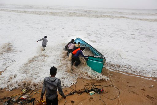 (AP Photo/Ajit Solanki). People try to move a fishing boat to a safer ground on the Arabian Sea coast in Veraval, Gujarat, India, Thursday, June 13, 2019. Authorities have evacuated nearly 300,000 people from India's western coastline ahead of a very s...