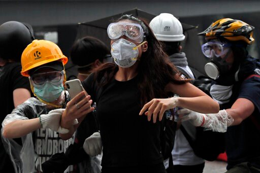 (AP Photo/Kin Cheung). In this photo taken on Wednesday, June 12, 2019, protesters flee after police fired tear gas during a massive demonstration outside the Legislative Council in Hong Kong. Young Hong Kong residents protesting a proposed extradition...
