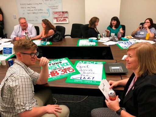 (AP Photo/Sarah Zimmerman). This June 12, 2019 photo public defenders in Oregon strategize at the Oregon Capitol in Salem, Oregon before lobbying lawmakers to pass legislation that would overhaul the public defender system in the state. Public defense ...
