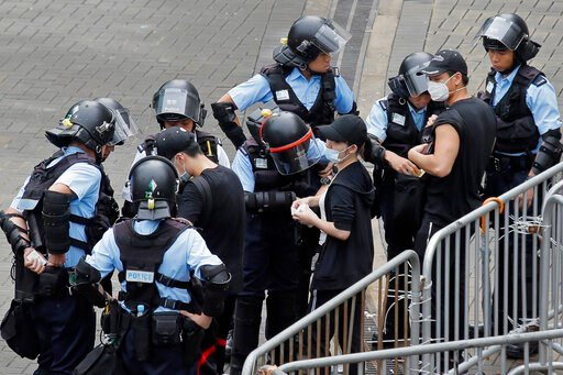 "(AP Photo/Kin Cheung). Riot police check the bags of protesters outside the Legislative Council in Hong Kong, Thursday, June 13, 2019. After days of silence, Chinese state media is characterizing the largely peaceful demonstrations in Hong Kong as a ""r..."