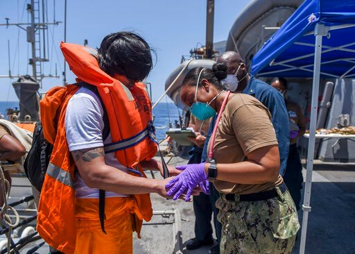 (Mass Communication Specialist 3rd Class Jason Waite, U.S. Navy via AP). In this June 13, 2019, photo released by the U.S. Navy, sailors aboard the Arleigh Burke-class guided-missile destroyer USS Bainbridge render aid to the crew of the Kokuka Courage...