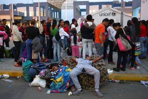 (AP Photo/Martin Mejia). Venezuelan migrants rest while another group stands in line to enter am immigration office in Tumbes, Peru, Friday, June 14, 2019. Venezuelan citizens are rushing to enter Peru before the implementation of new entry requirement...