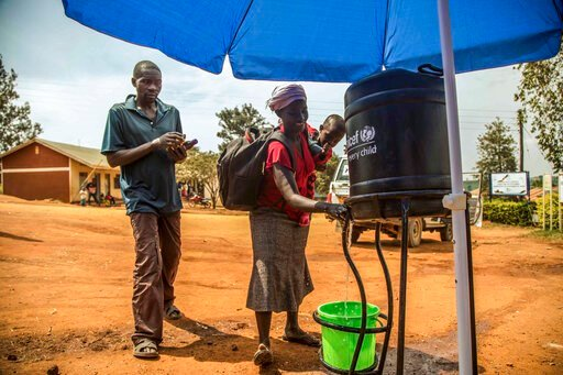 (Kellie Ryan/International Rescue Committee via AP). In this photo provided by the International Rescue Committee, Congolese refugees wash their hands before being screened for Ebola symptoms at the IRC triage facility in the Kyaka II refugee settlemen...