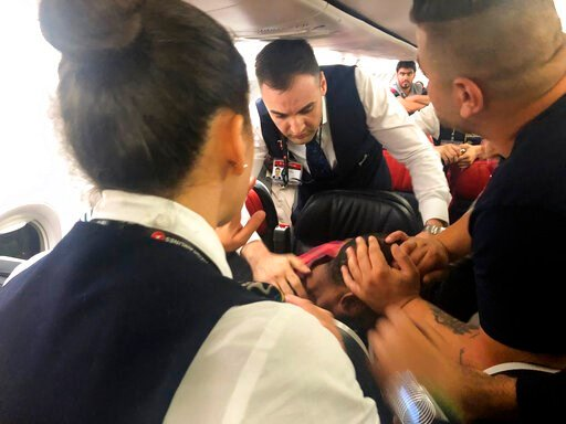 (AP Photo/Hussein Malla). The scene as Associated Press photographer Hussein Malla observes as passengers and crew aboard a Turkish Airlines jetliner subdue a man who started screaming a few minutes after takeoff from Istanbul. Turkey, Friday June 14, ...