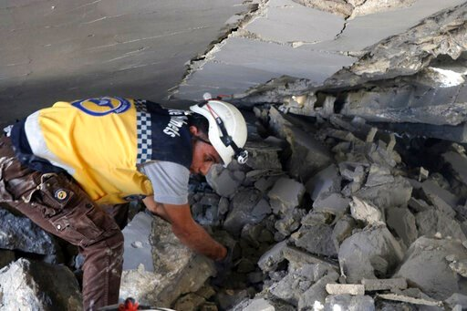 (Syrian Civil Defense White Helmets via AP). This photo posted and provided by the Syrian Civil Defense White Helmets, which has been authenticated based on its contents and other AP reporting, shows a Civil Defense worker searching for victims under t...