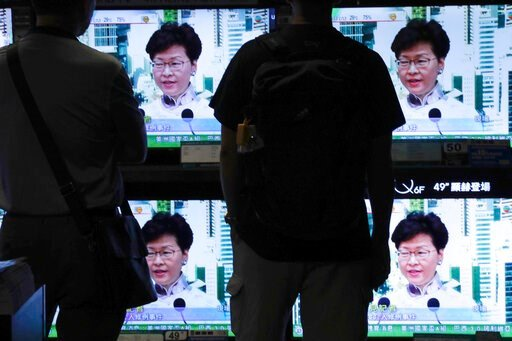 (AP Photo/Vincent Yu). Residents watch a broadcast of Chief Executive Carrie Lam speaking at a press conference held in Hong Kong on Saturday, June 15, 2019. Lam said she will suspend a proposed extradition bill indefinitely in response to widespread p...