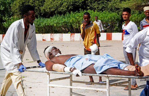 (AP Photo/Farah Abdi Warsameh). Medical workers help a man who was wounded in a bomb attack, at a hospital in the capital Mogadishu, Somalia Saturday, June 15, 2019.