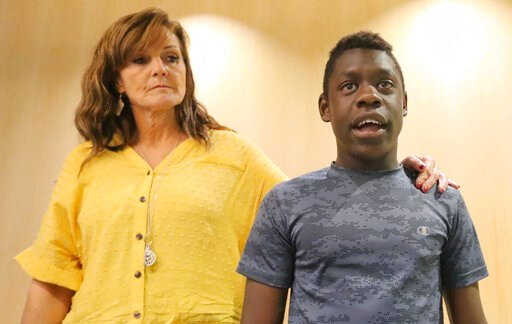 (AP Photo/Rick Bowmer). FILE - In this June 7, 2019 file photo, Jerri Hrubes stands next to her son DJ during a news conference Friday, June 7, 2019, in Salt Lake City.  About 100 protesters gathered outside a police agency, Friday, June 14,  to demand...