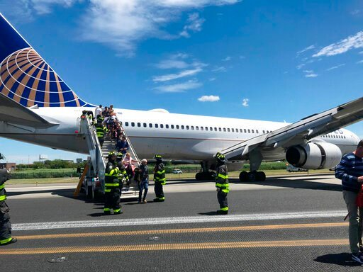 (Caroline Craddock via AP). This photo provided by Caroline Craddock shows emergency personnel help passengers off a plane after a  United Airlines plane skidded off the runway after landing at Newark Liberty International Airport on Saturday, June 15,...