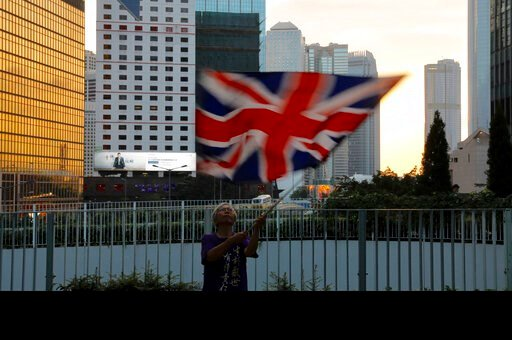 (AP Photo/Vincent Yu). A protester waves a British flag outside the government headquarters in Hong Kong on Saturday, June 15, 2019. Hong Kong's Chief Executive Carrie Lam said she will suspend a proposed extradition bill indefinitely in response to wi...
