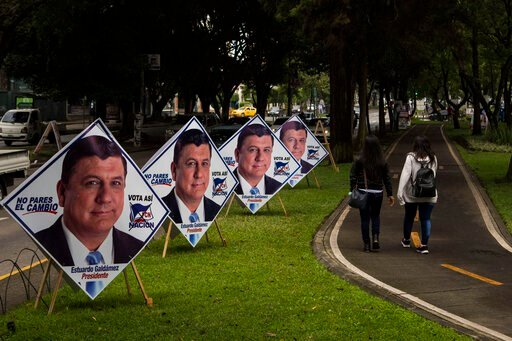 (AP Photo/Oliver de Ros). Women walk on the pedestrian path next to campaign posters promoting the ruling party presidential candidate Estuardo Galdamez, in Guatemala City, Saturday, June 15, 2019. The road to Sunday's presidential election in Guatemal...