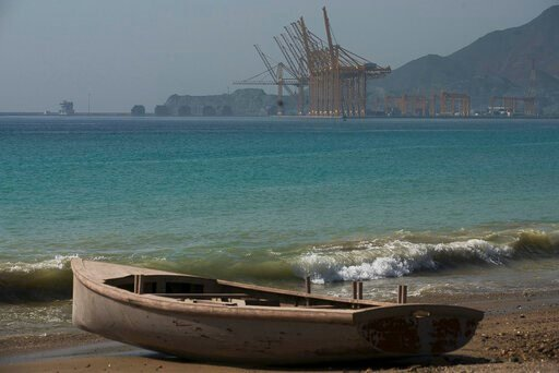 (AP Photo/Jon Gambrell). A wooden boat sits on the beach with the Port of Khorfakkan behind it in Khorfakkan, United Arab Emirates, Saturday, June 15, 2019. The Japanese owner of the Kokuka Courageous said Friday, June 14, 2019, that the vessel, one of...