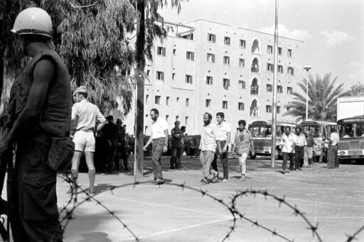 (Press and informations Office, via AP). This Sept. 19, 1974, photo provided from the Cyprus' press and informations office shows the Ledra Palace Hotel in the background during the exchange captive soldiers and civilians between Turkish and Cypriots a...