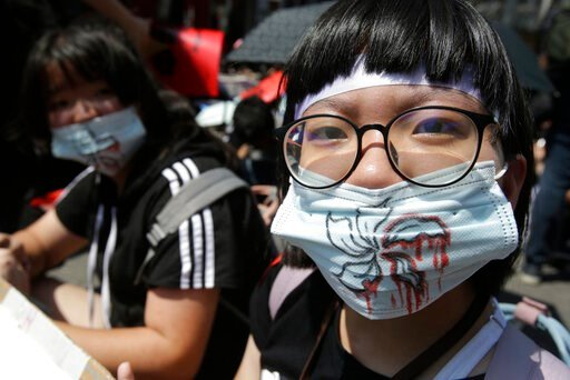 (AP Photo/Chiang Ying-ying). Supporters wear masks with bloody flowers painting for mourning to proposed extradition bill outside of the Legislative Yuan in Taipei, Taiwan, Sunday, June 16, 2019. Hong Kong residents Sunday continued their massive prote...