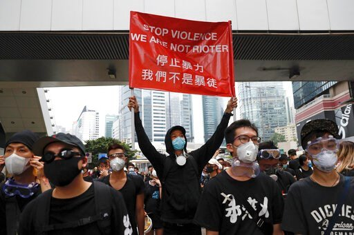 (AP Photo/Vincent Yu). Protesters hold a banner during a march toward the Legislative Council as they continue to protest against the extradition bill in Hong Kong, Monday, June 17, 2019. Hong Kong police announced that they want to clear the streets o...