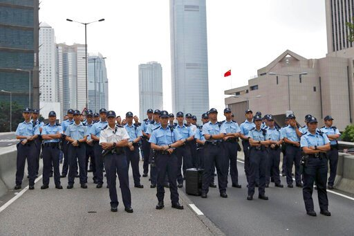 (AP Photo/Vincent Yu). Policemen stand guard on a road as protesters march toward the Legislative Council after they continue to protest against the extradition bill in Hong Kong, Monday, June 17, 2019. Hong Kong police announced that they want to clea...