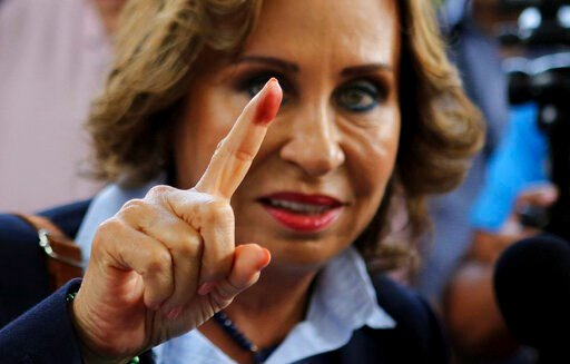 (AP Photo/Oliver de Ros). Sandra Torres, presidential candidate of the National Unity of Hope party, UNE, shows her ink stained finger to the press after casting her vote during general elections in Guatemala City, Sunday, June 16, 2019. Guatemalans ar...