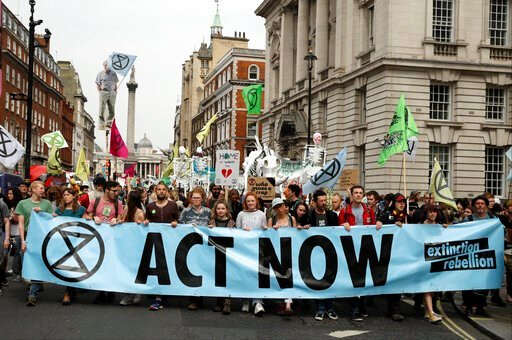 (AP Photo/Matt Dunham, file). FILE - In this Tuesday April 23, 2019 file photo, climate change protesters march along Whitehall toward parliament, in London. Britain's prime minister has announced plans to eliminate the country's net contribution to cl...