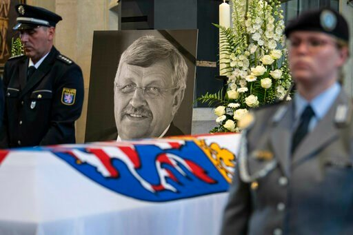 (Swen Pfoertner/dpa via AP). FILE-In this June 13, 2019 file photo a picture of Walter Luebcke stands behind his coffin during the funeral service in Kassel, Germany. German authorities say they have arrested a 45-year-old man in connection with their ...