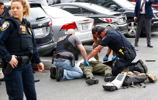 (Tom Fox/The Dallas Morning News). Law enforcement officers attend to an injured shooter in a parking lot after he fired shots at the Earle Cabell Federal Building in downtown Dallas, Monday, June 17, 2019.  MANDATORY CREDIT, NO SALES, MAGS OUT,  TV OU...